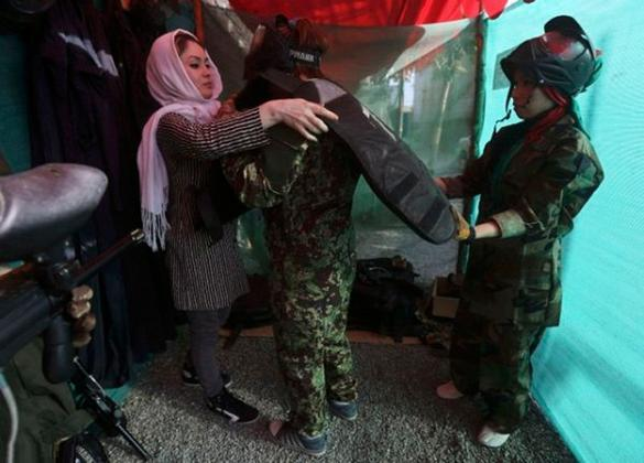 A member of Eagle paintball club helps an Afghan girl with her uniform before their paintball game at the paintball club in Kabul